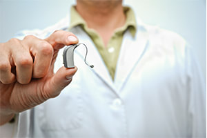 Dr. adjusting hearing aid